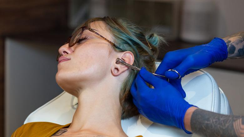Woman getting ear pierced