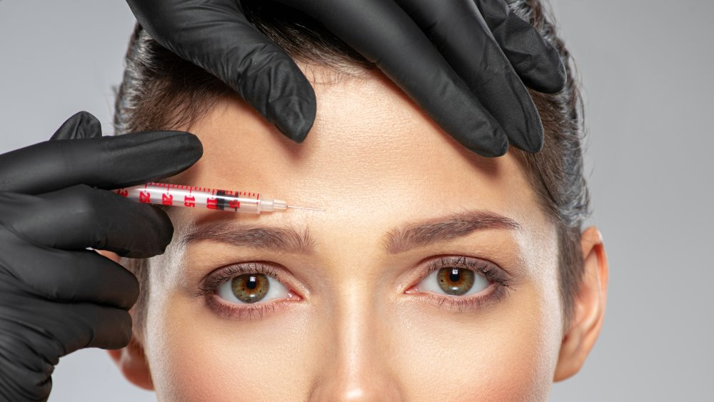 A needle being used near a woman's forehead