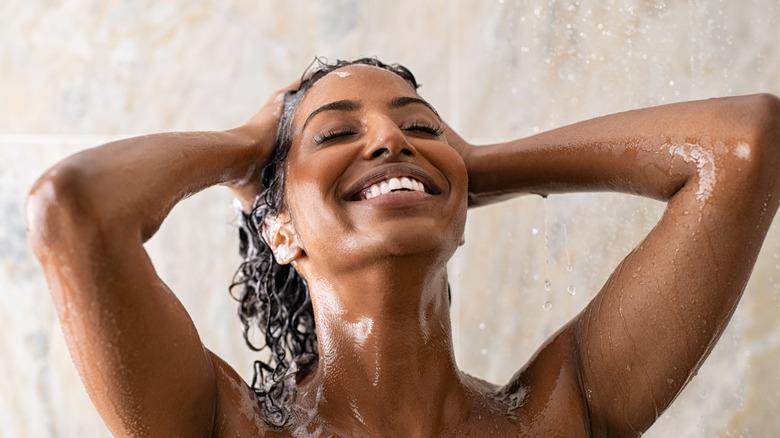 Woman washing her hair with shampoo