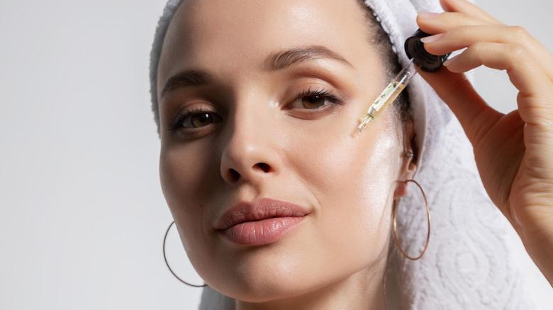 Woman smiling and applying facial serum
