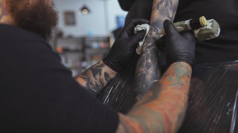 Tattoo artist working on a sleeve tattoo