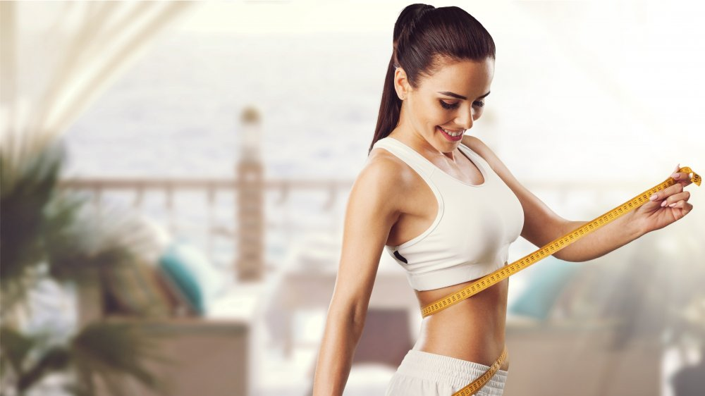 Woman measuring her waist after dieting