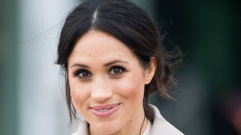 Meghan Markle smiling with an updo