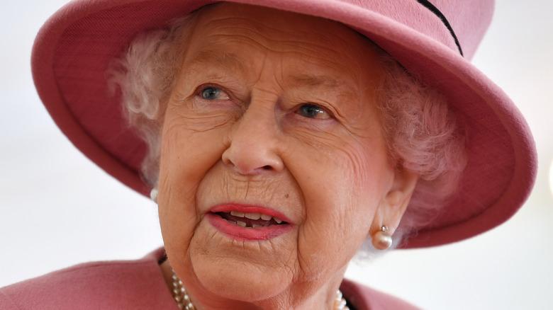 Queen Elizabeth in pink hat.
