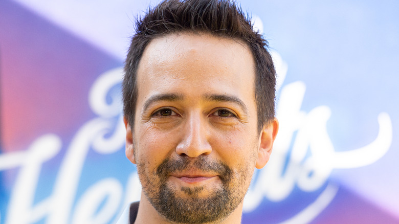 """Lin Manuel Miranda in front of an """"In the Heights"""" sign"""