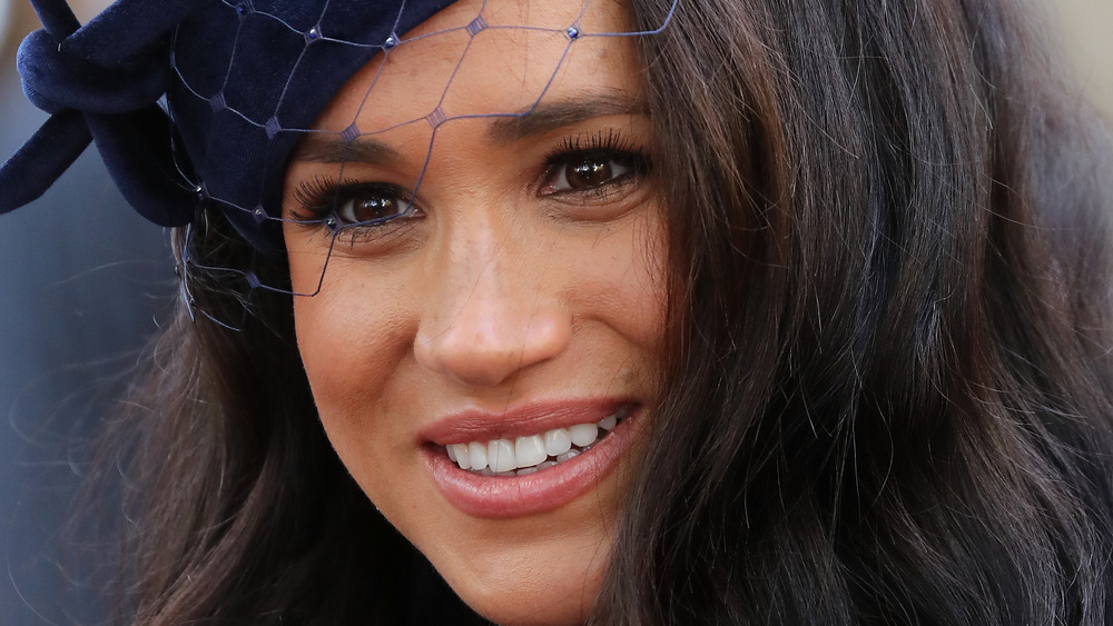 Meghan Markle smiling, wearing hat