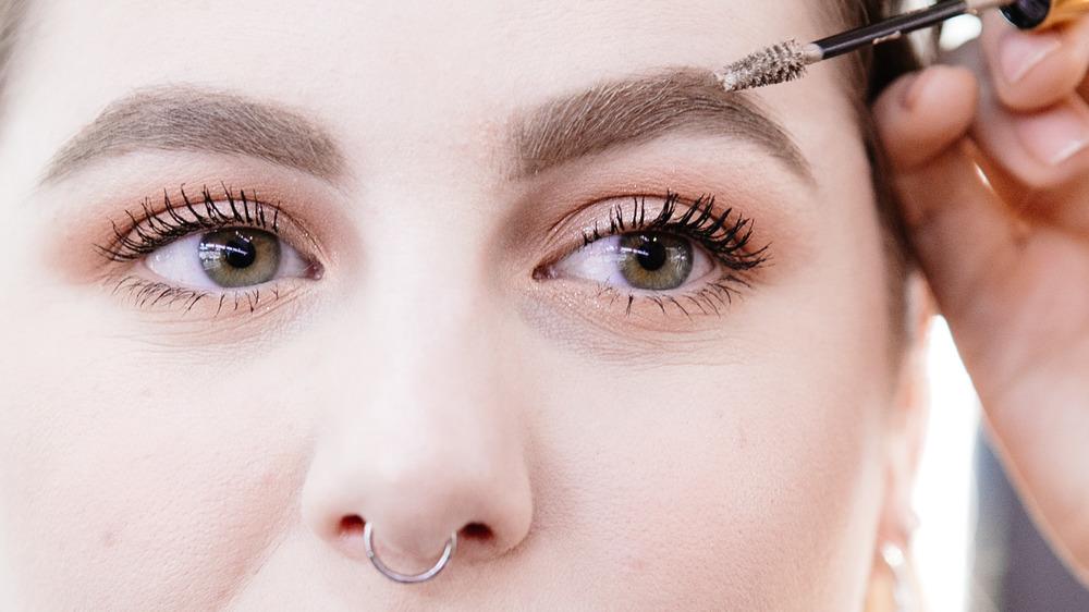 Woman applying eyebrow gel