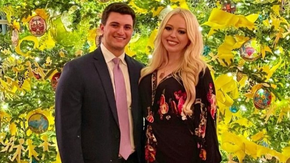 Tiffany Trump and her fiancé Michael Boulos pose in front of a Christmas treee
