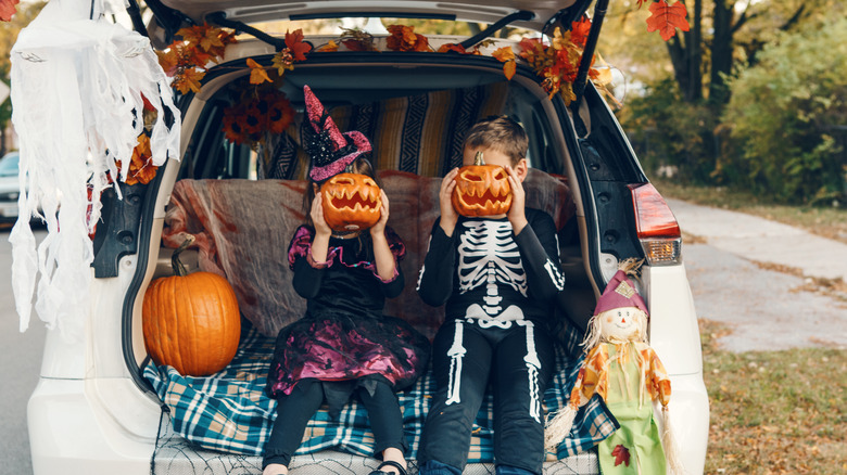 Kids posing in the back of a car decorated for Halloween