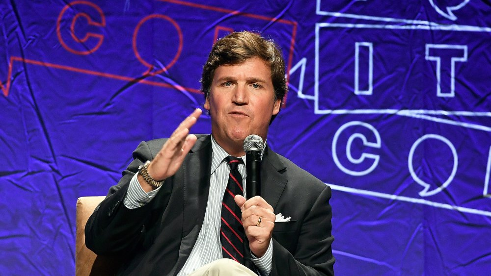 Tucker Carlson, on stage holding a microphone