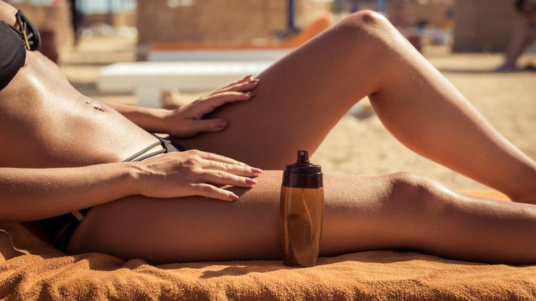 woman applying tanning oil