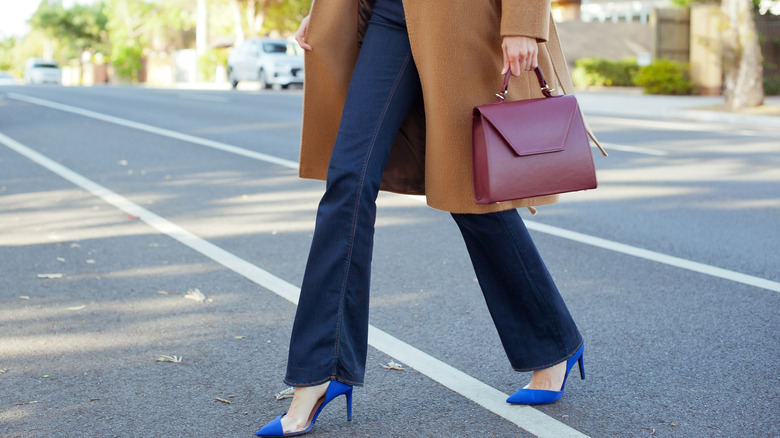 Stylish woman walking with tan briefcase, flared jeans and blue heels