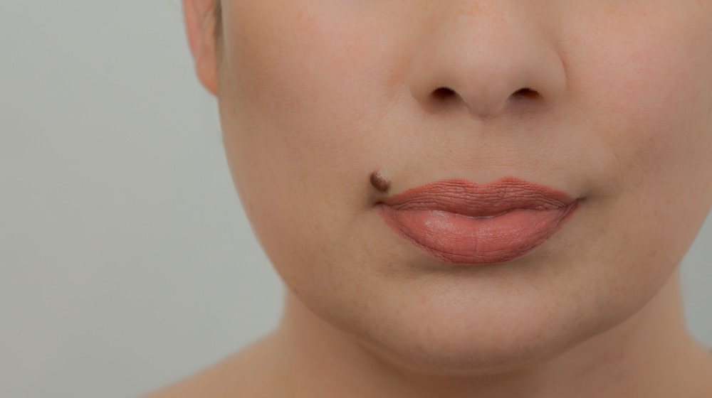Woman with a beauty mark near her full pink lips