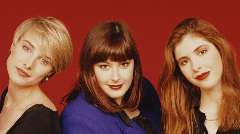 An archival photo of Wilson Phillips smiling against a red background