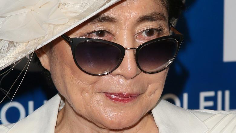 Yoko Ono wearing sunglasses and hat