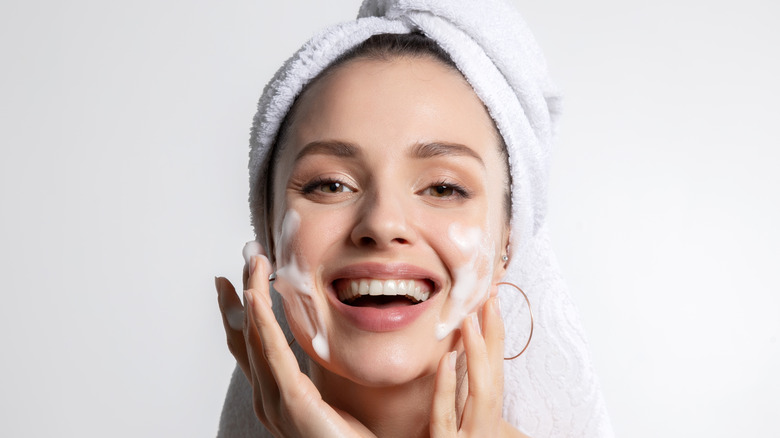 Woman cleaning face with towel on head