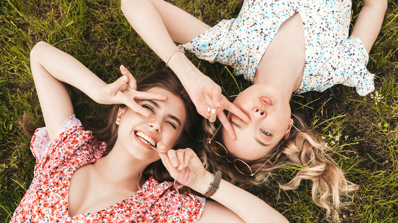 Two girls laying in grass