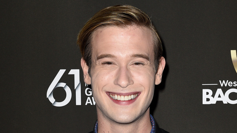 Tyler Henry in a leather jacket with a big smile