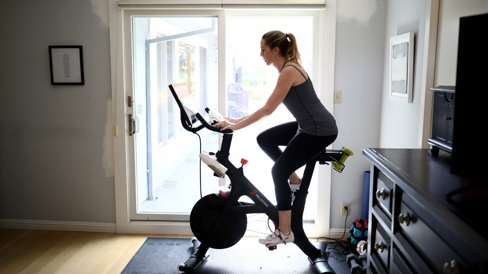 A woman using her Peloton in the living room