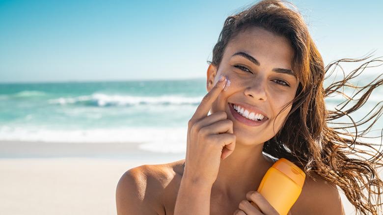 A woman applies sunscreen