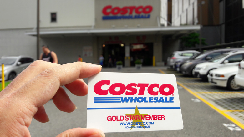 Hand holding Costco card outside of Costco