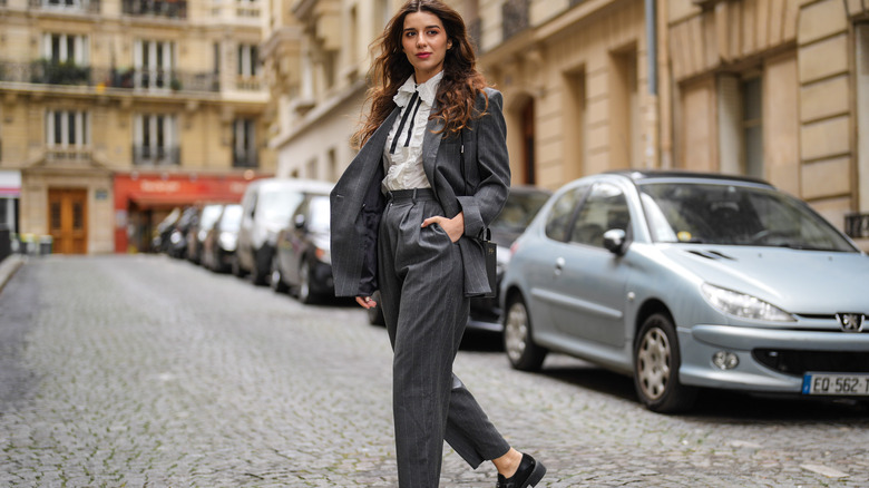 """Giorgadze @katie.one wears gray tailored tapered pinstripe wool trousers from &OtherStories, a gray oversized asymmetric pinstripe blazer jacket from &OtherStories, classic masculine black leather loafers from Prada, a white ruffled emrboidered """"broderie anglaise"""" cotton shirt with a black ribbon"""