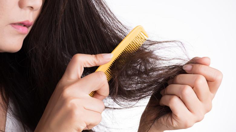 Woman brushing damaged hair