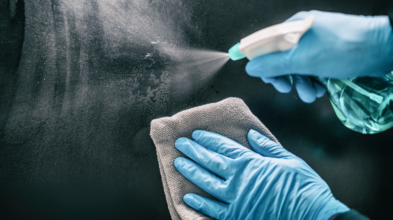 Blue gloved hands spraying cleaner