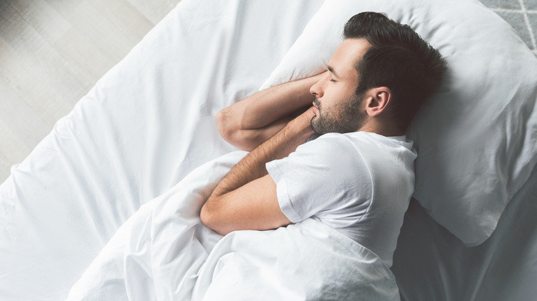 Man sleeping in a bed with off-white bedding