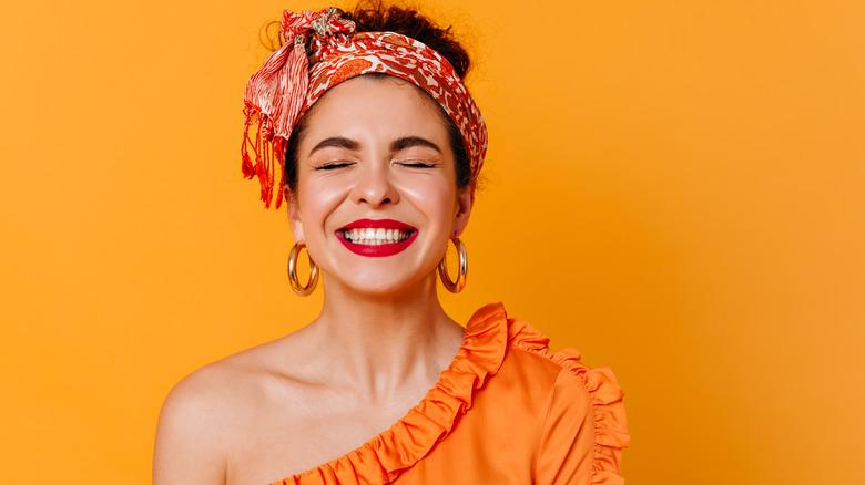 Woman in orange smiling
