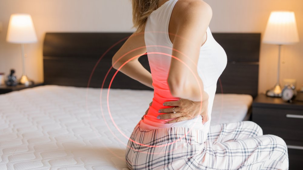 Woman on bed with back pain