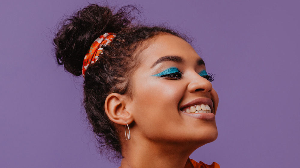 Girl with a high hair bun and blue eyeshadow