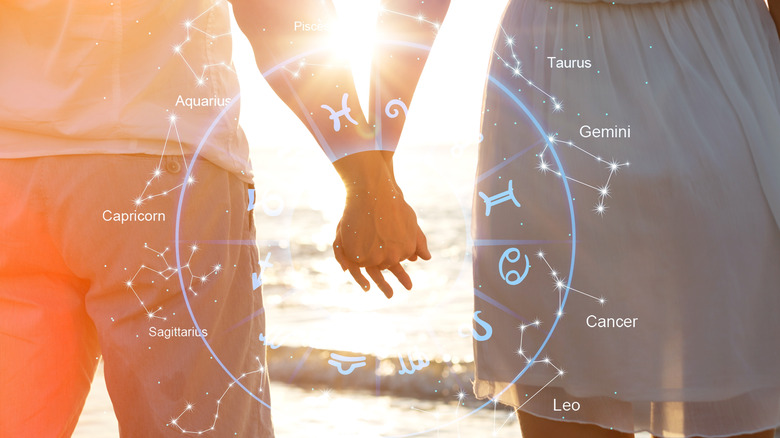 Couple holding hands in front of zodiac sign