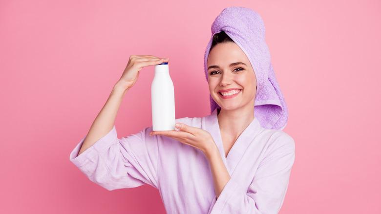 Woman holding shampoo bottle