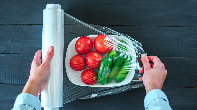 Person covering vegetables in plastic wrap
