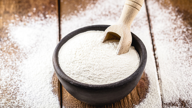 A bowl of flour on a wooden table