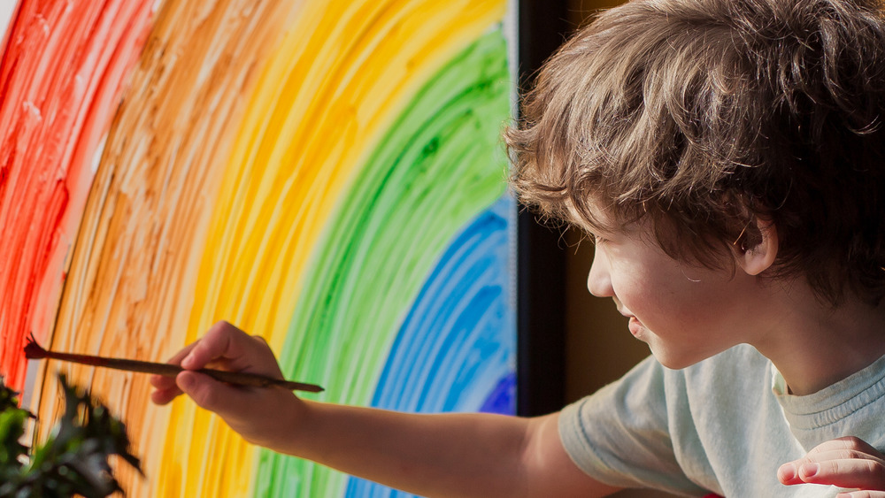 Kid painting rainbow on window