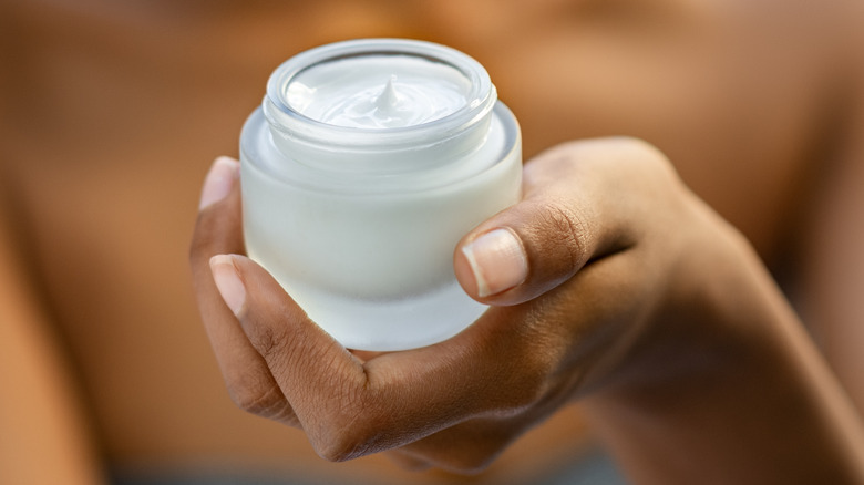 Woman holding a jar of face cream in her hands