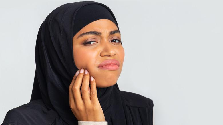 Woman touching her cheek, looking upset