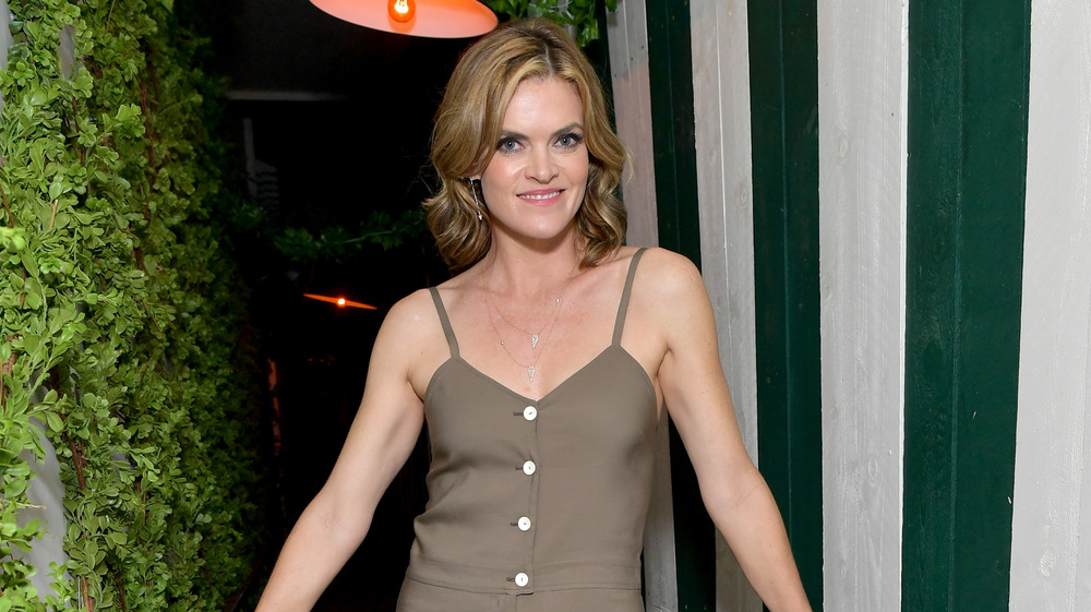 Smiling Missi Pyle in jumpsuit