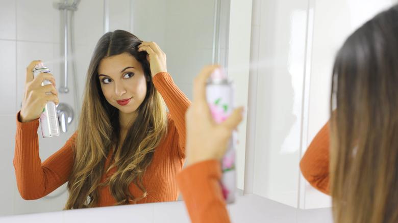 woman spraying dry shampoo into hair