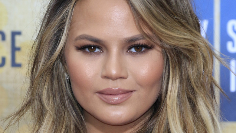 Chrissy Teigen poses with a soft smile