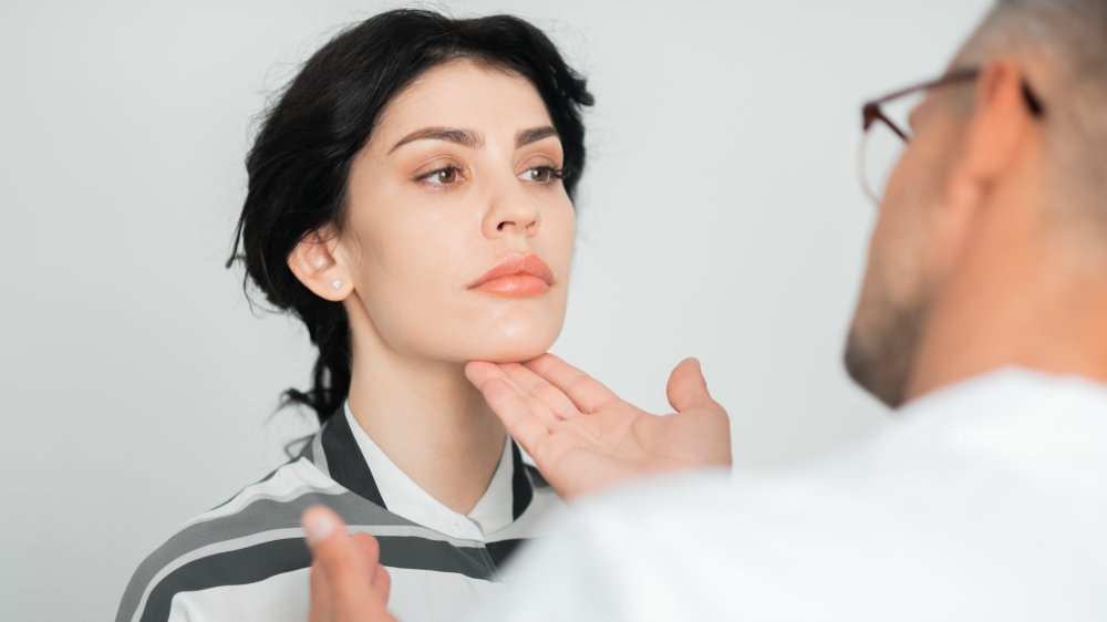 Plastic surgeon checking a woman's chin