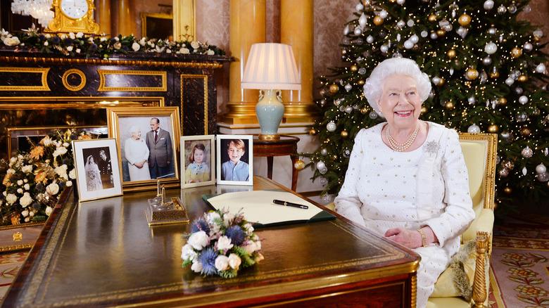 Queen Elizabeth at desk with photos