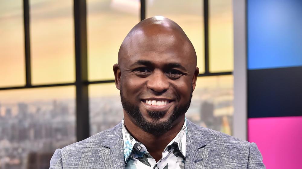 Wayne Brady smiling in a gray suit