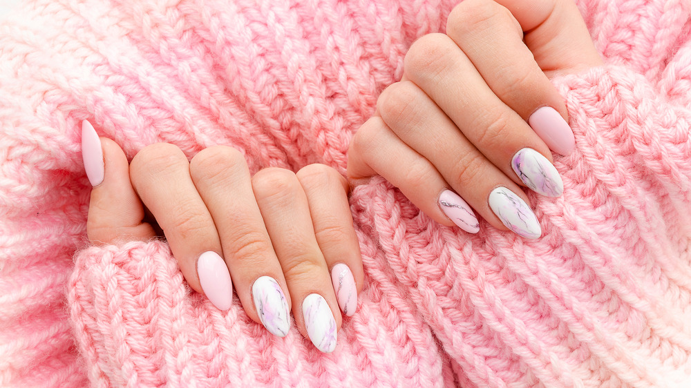 Closeup of manicured fingernails on woman in a pink sweater.