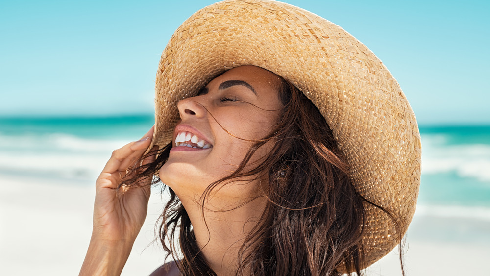 Woman smiles with a sunhat at the beach