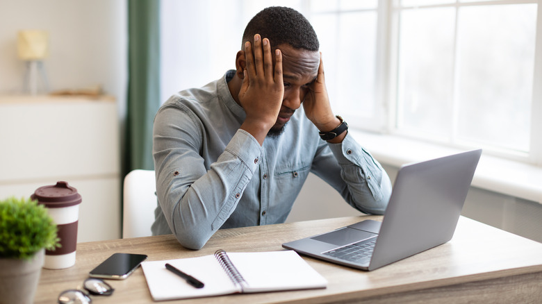 Man stressed at a computer