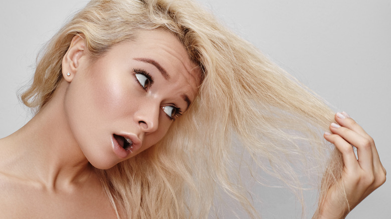 Woman looking at bleached hair