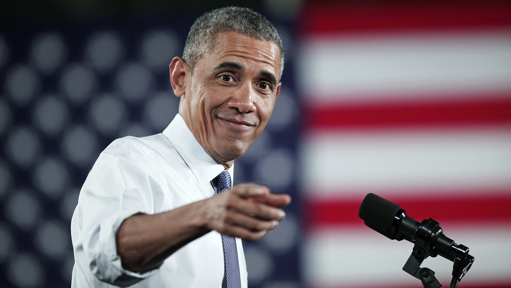 Barack Obama pointing and smiling at a podium